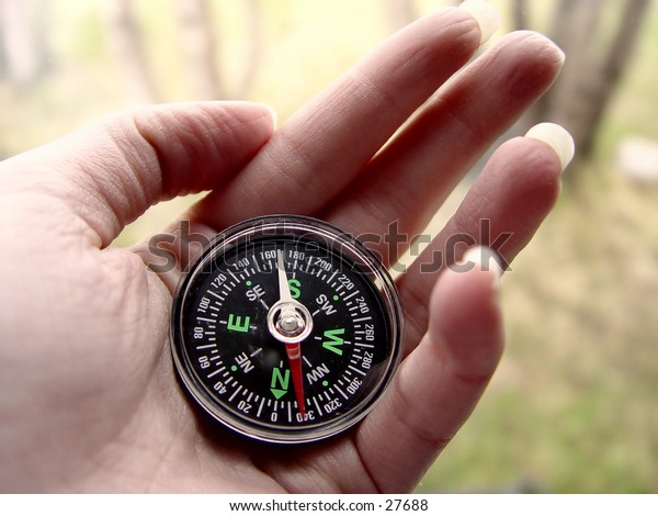 Female with compass in her hand in the woods