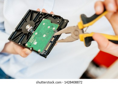 Female IT computer repair IT woman using yellow metal pliers to fix broken poor manufacture HDD disk drive with valuable stored data information