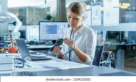 Female Computer Scientists Connects Circuit Board to Her Laptop and Starts Programming it. She Works in the Technologically Advanced Laboratory.