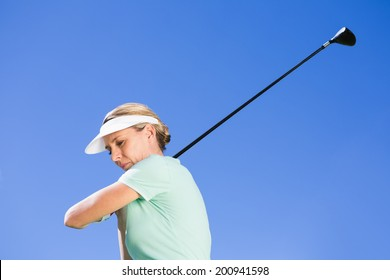 Female concentrating golfer taking a shot on a sunny day at the golf course