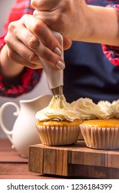 Female confectioner in a blue apron and a plaid red shirt applies cream to cupcakes from a pastry bag