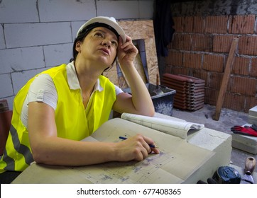 Female construction engineer in the field.  Compares the works with the project