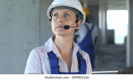 Female construction engineer reading plans and talk to workers through internal links