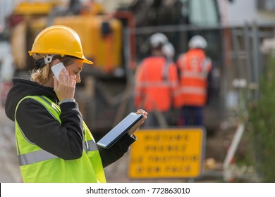 female construction woman using electronics on construction site
