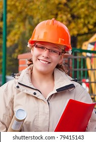 A female construction worker with building area behind