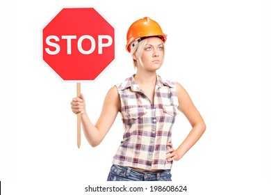 Female construction worker holding a stop sign isolated on white background