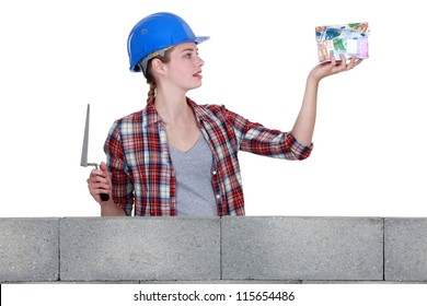 Female construction worker with a house made of money