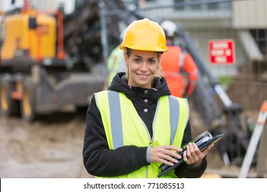 female construction worker managing team at building site