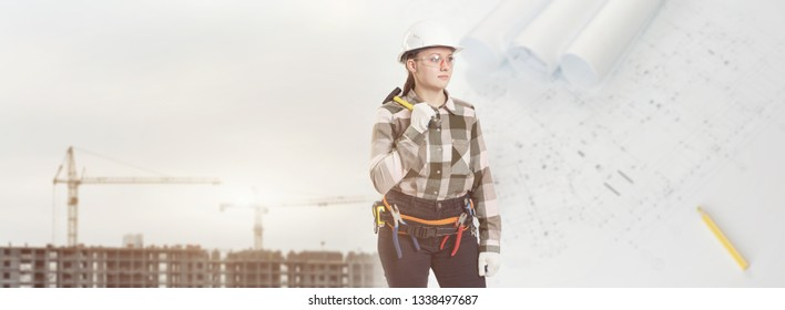 A female construction worker in safety helmet holds a hammer