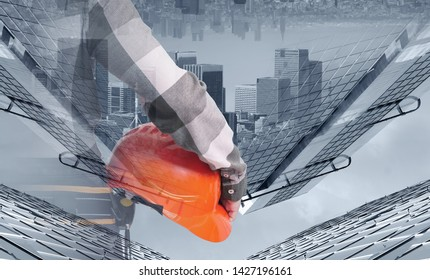 A female construction worker with safety helmet against city background