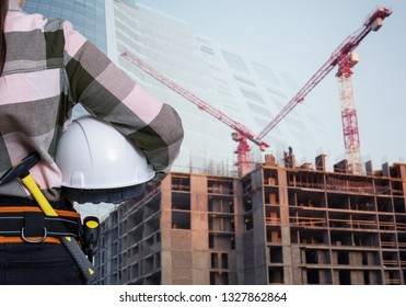 A female construction worker with white helmet against city background