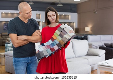Female consultant helping man choosing upholstery fabric in furniture shop. Focus on both persons