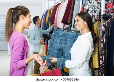Female consultant helping young customer shopping at apparel store