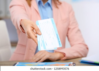 Female consultant holding tickets in travel agency, closeup