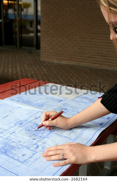 Female contractor looking at blueprints