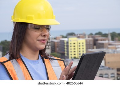 Female contractor at a work site using an ipad/tablet