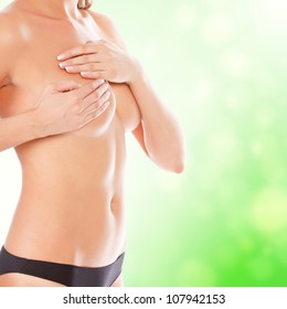 Female controlling breast for cancer, green blurred background.