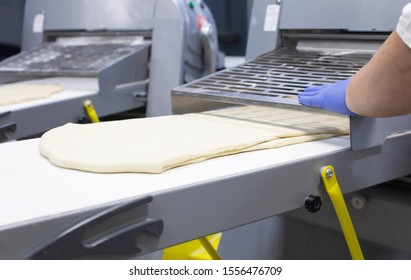 Female cook rolls dough on a dough sheeter to make pizza and puff pastry, modern technology