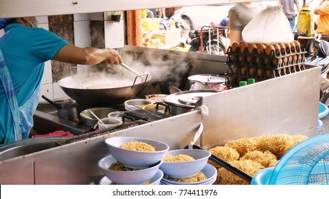 Female cooker was stir frying noodle in preparation for making 'Kuay Tiao Rad Na' (a stir fried noodle with pork and kale in sticky soup) at shop in Yaowarat, Bangkok, Thailand during lunch time