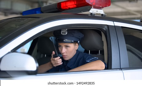 Female cop talking on walkie-talkie, responding emergency call, crime prevention