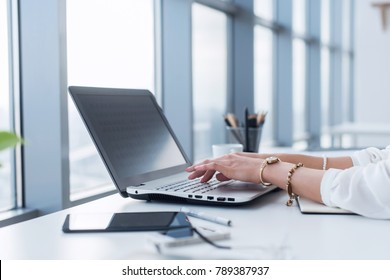 Female copywriter at her workplace, home, writing new text using laptop and Wi-Fi internet connection in the morning.