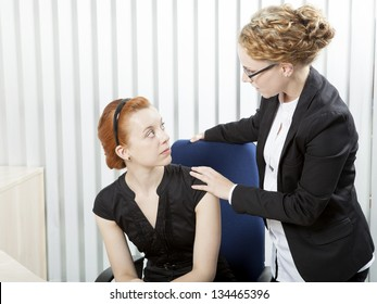 Female corporate supervisor talking to an employee laying a comforting hand on her shoulder as she tells her she is about to be made redundant
