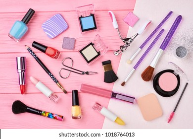 Female cosmetics products set, top view. Makeup cosmetics, brushes and other essentials on pink background. Flat lay of fashion beauty items.
