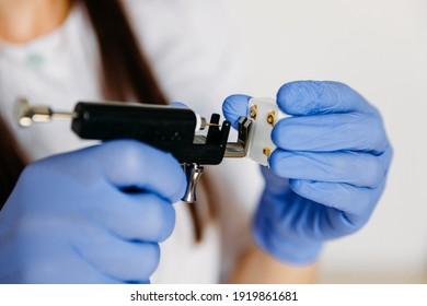 Female cosmetologist holding earrings and ear piercing gun