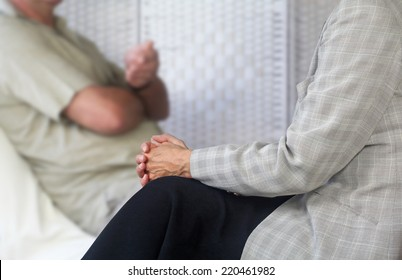 Female Counseling therapist in foreground listening to male patient sat on couch with client being soft focus in background