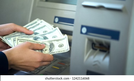 Female counting dollars withdrawn from ATM, 24h service, easy banking operation