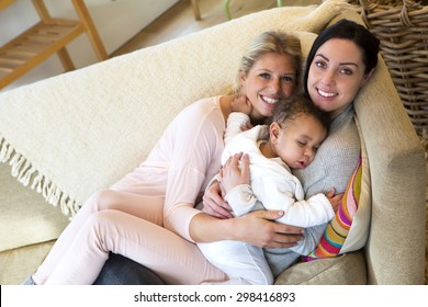 female couple cuddling on the sofa with their sleeping son