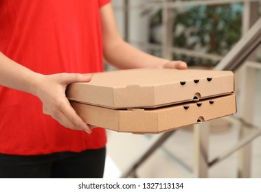 Female courier with pizza boxes indoors, closeup. Food delivery service