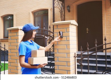 Female courier in uniform ringing in doorbell