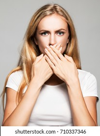 Female covers her mouth with her hands. Silence, fear, violence. Woman with closed mouth.