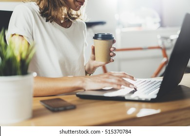 Female coworker using laptop while sitting at modern workspace and drinking coffee to go, businesswoman work process concept, professional young manger woman working at office via portable computer