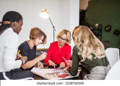 Female co-workers discussing together commercial project collaborating with team leaders supervising staff job. Multi- ethnic MLM team at working process.