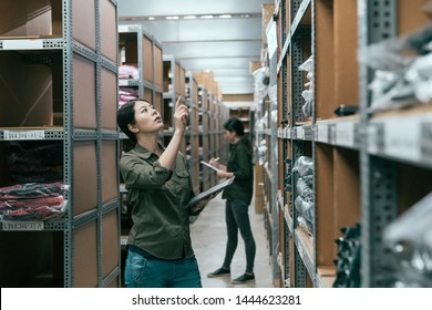 female coworkers taking inventory in logistics warehouse. young girl team partners standing in stockroom working. two woman staffs stocktaking by using tablet and clipbaord indoor in clothes factory