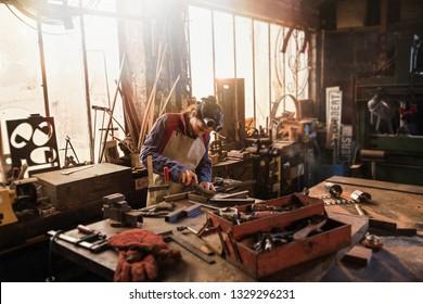 A female craftsman welder in her craft workshop working on a metal piece
