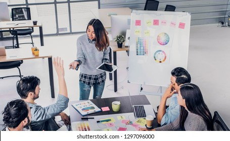 Female Creative director team lead brainstrom branding project with designer team hand up to ask question at meeting table.discussion idea in creative office