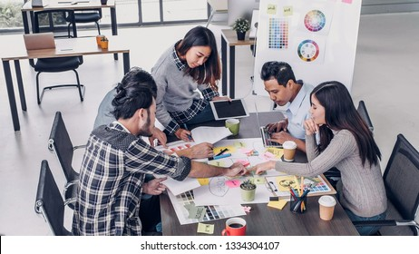 Female Creative director team leader brainstorm branding project with designer team at meeting table.discussion idea in creative office
