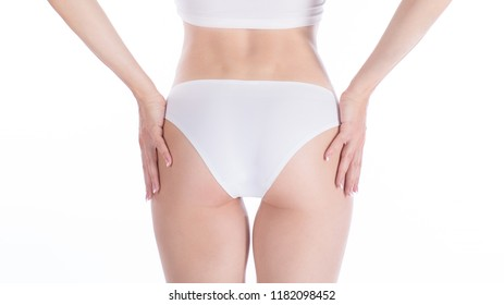 Female cropped fit buttocks in white base underwear, isolated on white. Woman lays her hands on her hips.