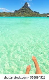 Female crossed legs over tropical blue lagoon and Otemanu mount, Bora Bora, near Tahiti, in French Polynesia. Vertical composition
