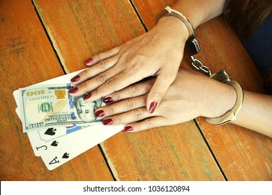 Female cuffed hands on money and playing cards over a woody table