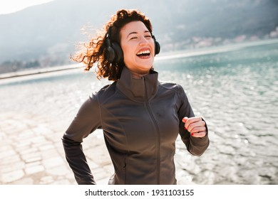 Female with curly hair runner jogging during outdoor workout on beach listening to music in earphones.