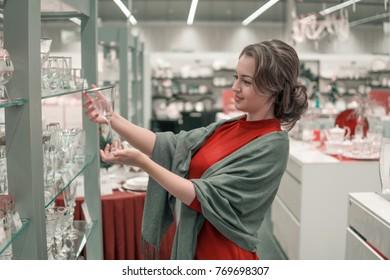 female customer choosing crystal glasses utensil dishes in the supermarket mall