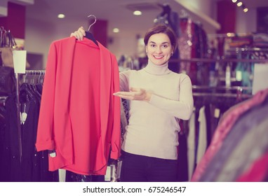 Female customer deciding on jersey cardigan in womens cloths shop