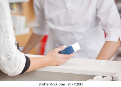 Female customer holding medicine box with pharmacist at counter