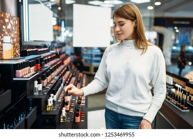 Female customer looking cosmetics in makeup shop