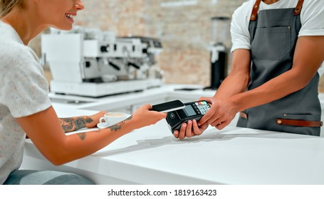 Female customer making payment through mobile phone at counter in cafe with young man. Barista holding credit card reading machine in front of female costumer with cell phone.