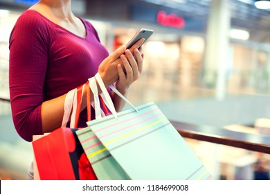 Female customer with mobilephone and shopping bags in the mall